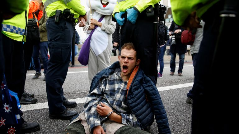 Ann activist in handcuffs shouts as he sits at Westminster Bridge during the Extinction Rebellion protest in London, Britain October 7, 2019. REUTERS/Henry Nicholls