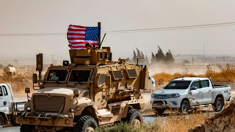 A US soldier sits atop an armoured vehicle during a demonstration by Syrian Kurds against Turkish threats next to a base for the US-led international coalition on the outskirts of Ras al-Ain town in Syria's Hasakeh province near the Turkish border on October 6, 2019. - US forces in Syria started pulling back today from Turkish border areas, opening the way for Ankara's threatened military invasion and heightening fears of a jihadist resurgence. (Photo by Delil SOULEIMAN / AFP) (Photo by DELIL SOULEIMAN/AFP via Getty Images)