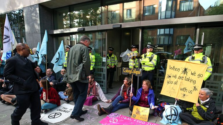 People enter the Department for Environment, Food and Rural Affairs, Marsham Street, passing police and protesters during an Extinction Rebellion (XR) protest in Westminster, London.