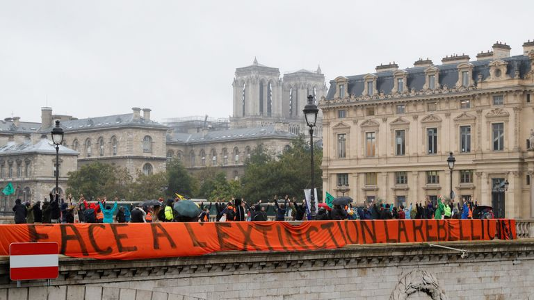 "Protestors hold a sign reading ""In the face of extinction, rebellion"" during a demonstration called by climate change activist group Extinction Rebellion, on October 8, 2019, on the Pont au Change bridge in Paris. - Climate protesters from Sydney to London blocked roads starting on October 7, sparking mass arrests at the start of two weeks of civil disobedience demanding immediate action to save the Earth from ""extinction"". The year-old group Extinction Rebellion has energised a global movement demanding governments drastically cut the carbon emissions that scientists have shown to cause devastating climate change. (Photo by Thomas SAMSON / AFP) (Photo by THOMAS SAMSON/AFP via Getty Images)"