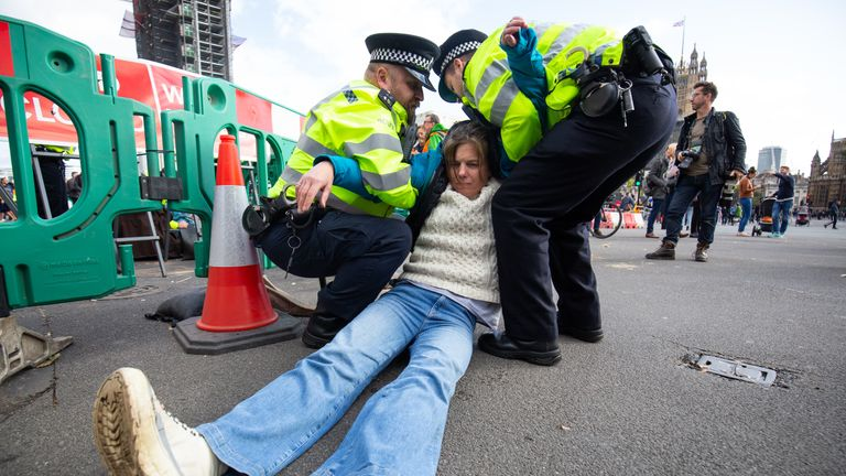 Police remove a demonstrator during an Extinction Rebellion (XR) protest in Westminster, London.