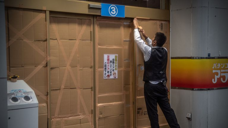 TOKYO, JAPAN - OCTOBER 12: A man covers over a doorway to a pachinko parlour ahead of the arrival of Typhoon Hagibis on October 12, 2019 in Tokyo, Japan. Typhoon Hagibis is the most powerful typhoon to hit Japan this year and has been classed by the Japan Meteorological Agency as a 'violent typhoon' - the highest category on Japans typhoon scale. (Photo by Carl Court/Getty Images)