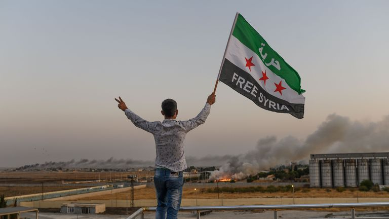 """A man waves a Syrian opposition flag reading """"Free Syria"""" on October 13, 2019 in Akcakale as smoke rises in the background from the Syrian border city of Tal Abyad seized today by Turkish forces and their proxies, on the fifth day of a Turkish offensive in Syria against Kurdish-controlled areas of northeastern Syria. - The Syrian Observatory for Human Rights said the capture of Tal Abyad left the town of Ras al-Ain as the only other major target remaining in the initial phase of the five-day-old Turkish assault. (Photo by BULENT KILIC / AFP) (Photo by BULENT KILIC/AFP via Getty Images)"""