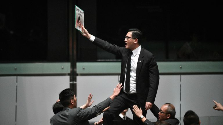 Pro-democracy lawmaker Lam Cheuk-ting (C) stands up and protests shortly before Hong Kong's Chief Executive Carrie Lam (not pictured) leaves the chamber for the second time while trying to present her annual policy address at the Legislative Council (Legco) in Hong Kong on October 16, 2019. - Hong Kong's embattled leader abandoned a State of the Union-style speech on October 16 after she was heckled by opposition lawmakers during chaotic scenes inside the city's legislature. (Photo by Anthony WALLACE / AFP) (Photo by ANTHONY WALLACE/AFP via Getty Images)