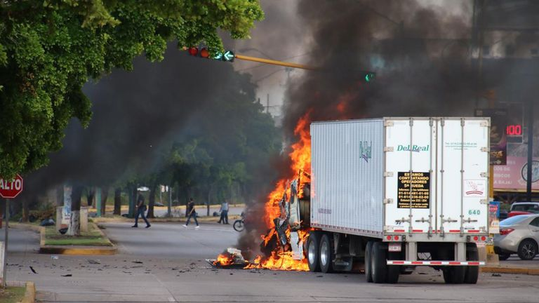 "A truck burns in a street of Culiacan, state of Sinaloa, Mexico, on October 17, 2019. - Heavily armed gunmen in four-by-four trucks fought an intense battle against Mexican security forces Thursday in the city of Culiacan, capital of jailed kingpin Joaquin ""El Chapo"" Guzman's home state of Sinaloa. (Photo by STR / AFP) (Photo by STR/AFP via Getty Images)"