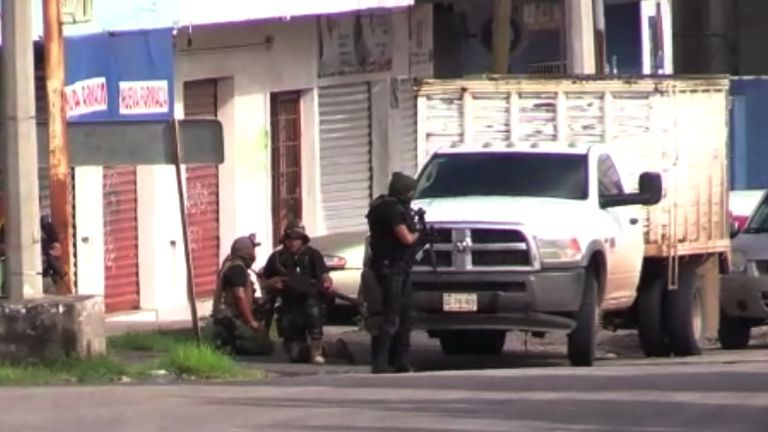 "In this AFPTV screen grab armed gunmen take position in a street of Culiacan, state of Sinaloa, Mexico, on October 17, 2019. - Heavily armed gunmen in four-by-four trucks fought an intense battle against Mexican security forces Thursday in the city of Culiacan, capital of jailed kingpin Joaquin ""El Chapo"" Guzman's home state of Sinaloa. (Photo by STR / AFP) (Photo by STR/AFP via Getty Images)"