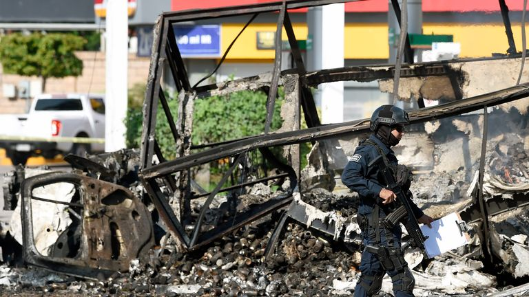 "A policeman walks past a burnt vehicle after heavily armed gunmen waged an all-out battle against Mexican security forces in Culiacan, Sinaloa state, Mexico, on October 18, 2019. - Mexico's president faced a firestorm of criticism Friday as his security forces confirmed they arrested kingpin Joaquin ""El Chapo"" Guzman's son, then released him when his cartel responded with an all-out gun battle. (Photo by ALFREDO ESTRELLA / AFP) (Photo by ALFREDO ESTRELLA/AFP via Getty Images)"
