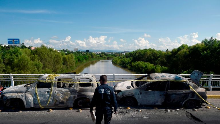 "A policeman stands next to burnt vehicles after heavily armed gunmen waged an all-out battle against Mexican security forces in Culiacan, Sinaloa state, Mexico, on October 18, 2019. - Mexico's president faced a firestorm of criticism Friday as his security forces confirmed they arrested kingpin Joaquin ""El Chapo"" Guzman's son, then released him when his cartel responded with an all-out gun battle. (Photo by ALFREDO ESTRELLA / AFP) (Photo by ALFREDO ESTRELLA/AFP via Getty Images)"