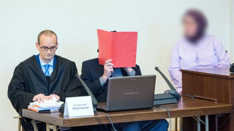 93-year-old former SS guard Bruno Dey (C) covers his face and sits next to his lawyer Stefan Waterkamp (L) and a relative (R) in the courtroom during his trial in Hamburg on October 21, 2019. - Dey stands accused of involvement in the murder of 5,230 people when he worked at the Stutthof concentration camp near what was then Danzig, now Gdansk in Poland. (Photo by Daniel Bockwoldt / POOL / AFP) (Photo by DANIEL BOCKWOLDT/POOL/AFP via Getty Images)