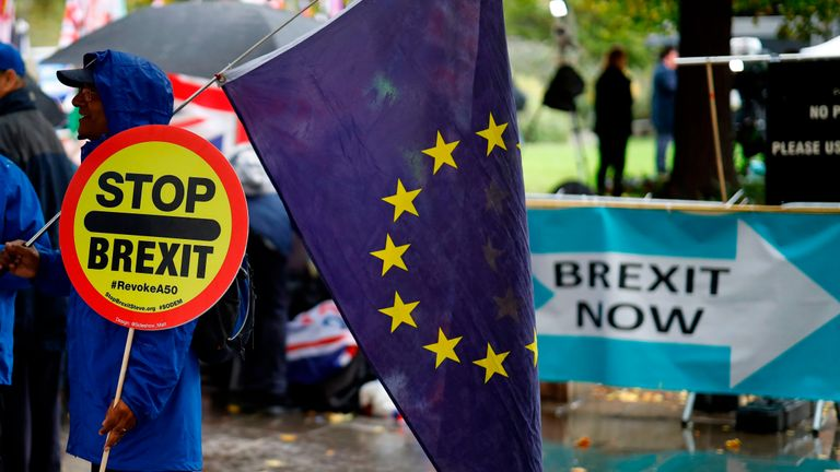 An anti-Brexiteer holds an EU flag near pro-Brexit banners outside the Houses of Parliament in Westminster, central London on October 17, 2019. - Britain's Prime Minister Boris Johnson and the European Union on Thursday reached a provisional agreement that might just see Britain leave the European Union by the October 31 deadline. (Photo by Tolga Akmen / AFP) (Photo by TOLGA AKMEN/AFP via Getty Images)