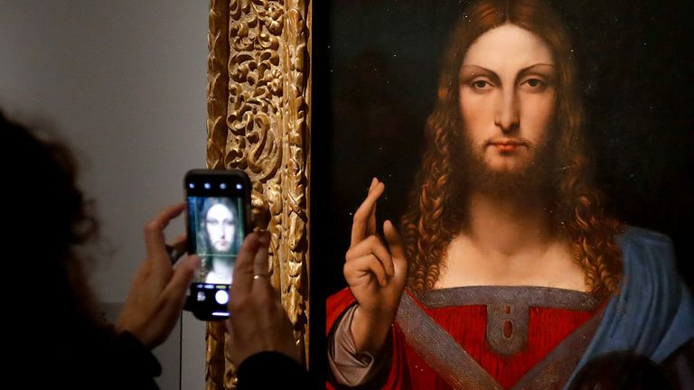 """People take pictures with mobile phone of an oil painting by Atelier Leonardo da Vinci's  """" Salvator Mundi"""" (Version Ganay), during the opening of the exhibition """" Leonardo da Vinci """", on October 22, 2019 at the Louvre museum in Paris. - Five hundred years after the death of Leonardo da Vinci, the Louvre Museum inaugurates on October 23, 2019 the largest exhibition ever set up around the work of the genius of the Renaissance, which is already announced as a popular success. (Photo by FRANCOIS GUILLOT / AFP) / RESTRICTED TO EDITORIAL USE - MANDATORY MENTION OF THE ARTIST UPON PUBLICATION - TO ILLUSTRATE THE EVENT AS SPECIFIED IN THE CAPTION (Photo by FRANCOIS GUILLOT/AFP via Getty Images)"""
