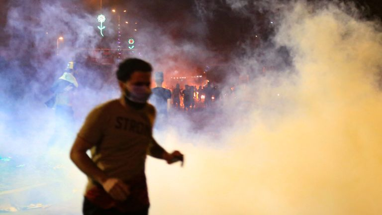 A protestr runs from tear gas smoke during anti-government protests in the Shiite shrine city of Karbala, south of Iraq's capital Baghdad, late on October 28, 2019. - Protests have persisted across Iraq and its Shiite-majority south, with night-time rallies in the central city of Karbala spiralling into skirmishes with security forces. (Photo by - / AFP) (Photo by -/AFP via Getty Images)