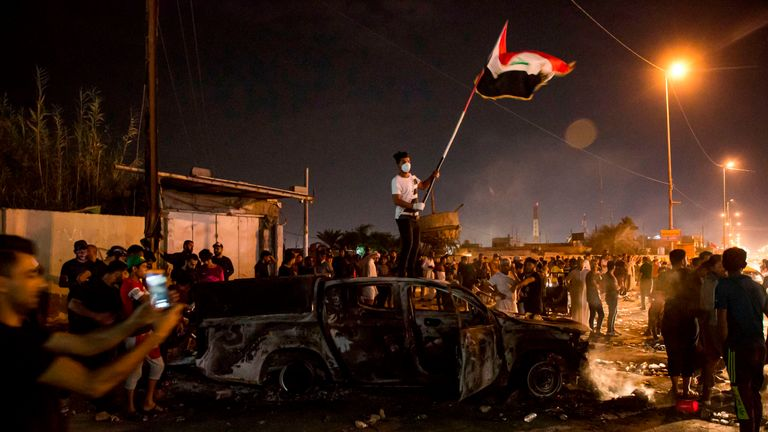 A protester waves a national flag as he stands on a burnt-out police vehicle in Basra