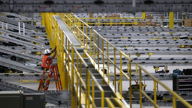 SACRAMENTO, CA - AUGUST 10: A worker makes repairs to a conveyor belt system that is under construction at a new Amazon fulfillment center on August 10, 2017 in Sacramento, California. Amazon is preparing to open a new 855,000-square-foot warehouse, the tenth in California, by early October and is expected to hire nearly 1,500 people. (Photo by Justin Sullivan/Getty Images)