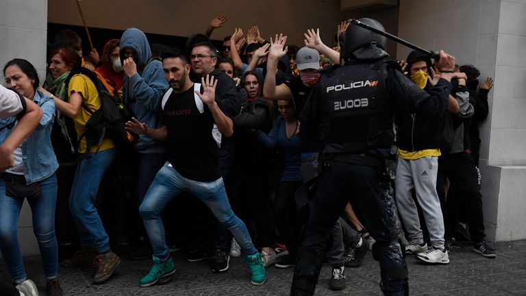 A policeman uses a baton to attack protesters near police headquarters in Barcelona