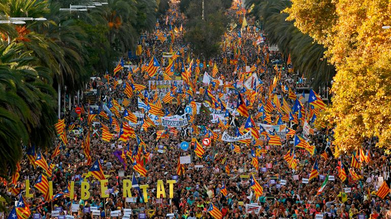 People wave Catalan pro-independence 'Estelada' flags during a peaceful pro-independence demonstration