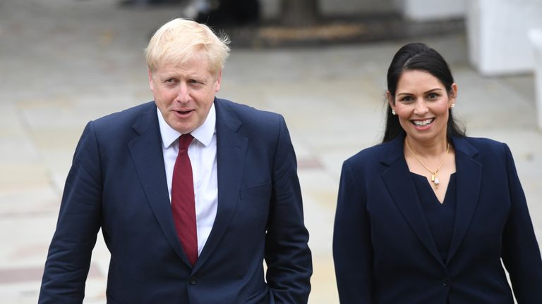 Prime Minister Boris Jonhson walks with Home Secretary Priti Patel at the Conservative Party conference