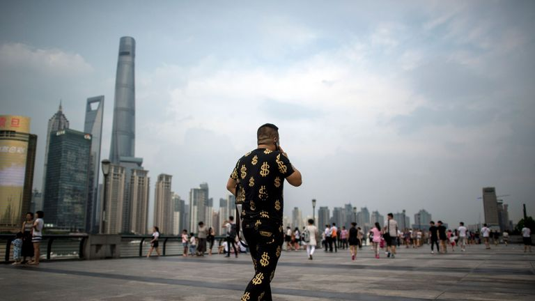 This picture taken on July 15, 2016 shows a man wearing an outfit with golden dollar symbols as he walks down the Bund overlooking the financial district of Pudong in Shanghai. China's second-quarter GDP growth was steady at 6.7 percent, the government said on July 15, as the world's second-largest economy seeks stability in the face of a darkening global outlook