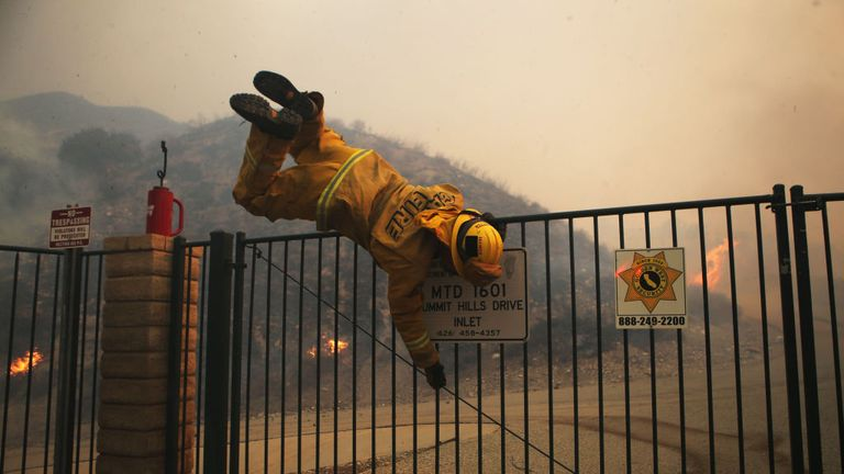 A firefighter hops over a locked gate near the Tick fire in Southern California