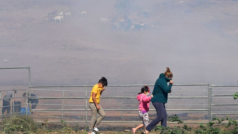 A family cover their faces from the smoke in Simi Valley