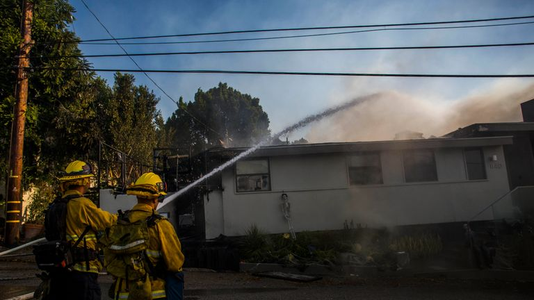 Firefighters 'damp down' in the LA suburb of Brentwood