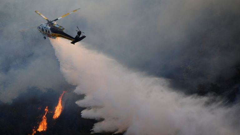 A helicopter drops water on a blaze on the outskirts of LA