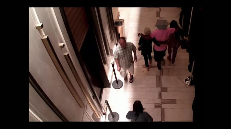 The suspects can be seen walking the man, wearing a pink shirt, out of the casino