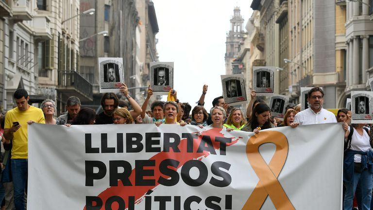 "Pro-independence supporters in Barcelona carry a banner reading ""Free political prisoners""after their sentencing"