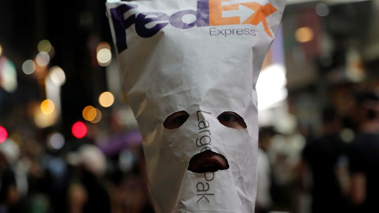 An anti-government protester wears a mask made with a FedEx envelope during a demonstration in Hong Kong, China