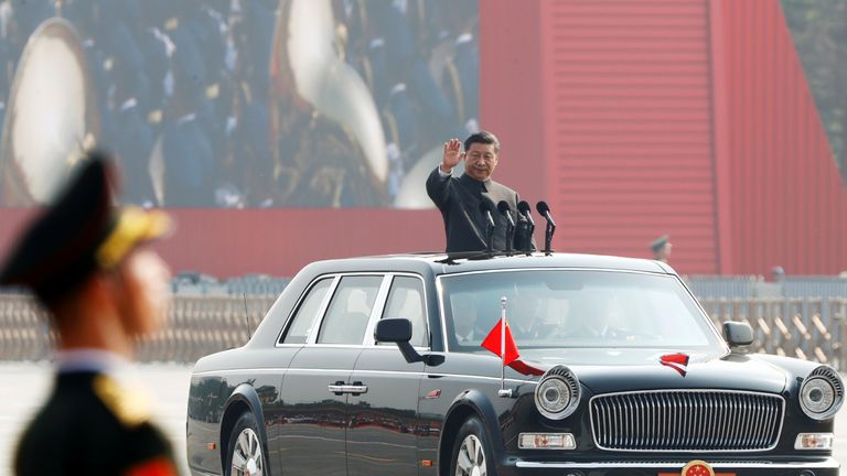 Chinese President Xi Jinping waves from a vehicle as he reviews the troops at a military parade marking the 70th founding anniversary of People's Republic of China, on its National Day in Beijing, China