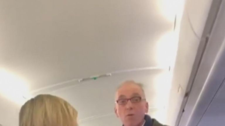 Protester stands up in aisle of plane at London City Airport