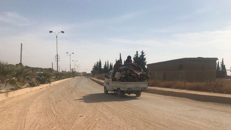 A family is seen leaving Derbasya on a truck
