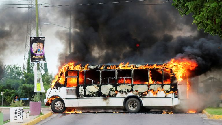 A burning bus pictured after a gun fight between Mexican police and the Sinaloa cartel