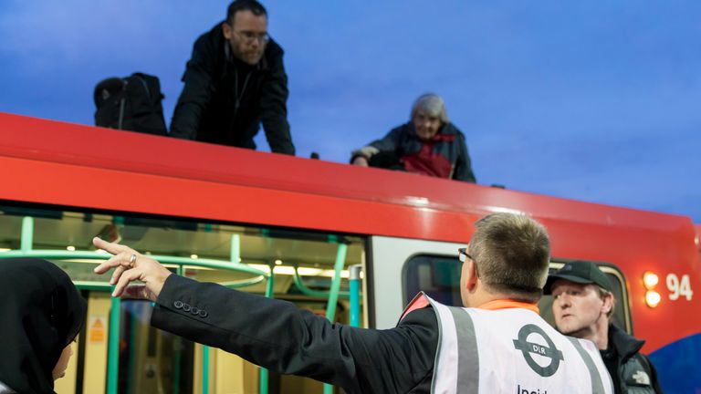 Members of Christian Climate Action Father Martin Newell (52, priest from Birmingham) and Rev. Sue Parfitt (77, from Bristol) climb on the roof of a DLR train at Shadwell station. Pic: : Vladimir Morozov/akxmedia.