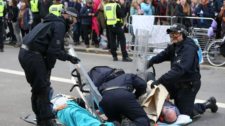 Police attempt to separate a pair of protesters who have glued themselves to each other adjacent to the Women of World War Two memorial on Whitehall