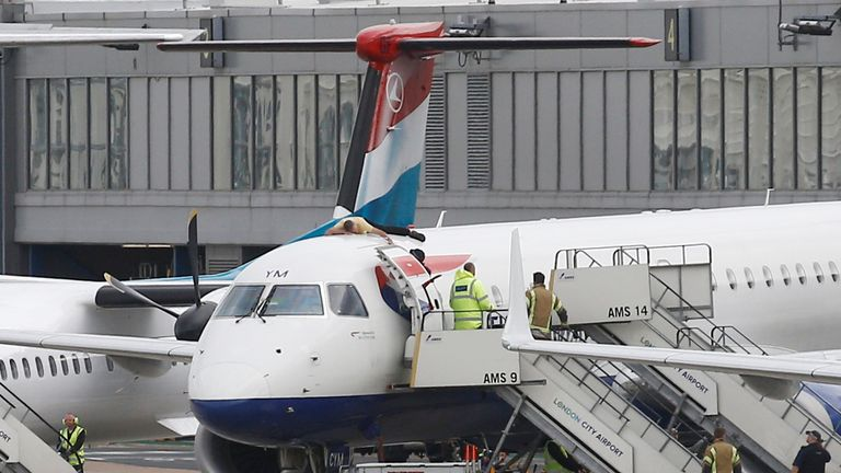 A protester, who Extinction Rebellion says is former Paralympic athlete James Brown, lies on top of a British Airways plane at London City Airport
