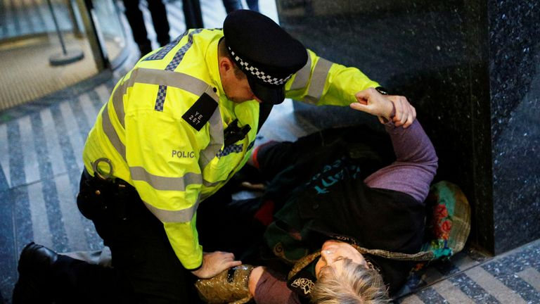 A police officer tries to remove a woman after she attached herself with an adhesive to the building of Department of Transport, during an Extinction Rebellion protest