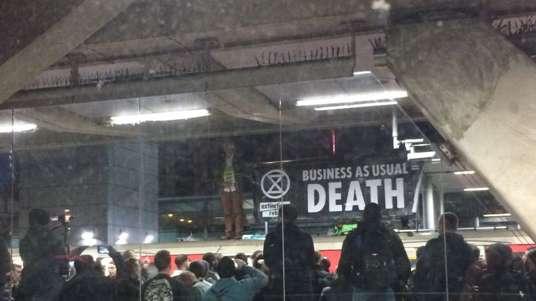 Two Extinction Rebellion protesters unfurled a banner on top of a Tube at Canning Town station in east London. Pic: Twitter/@GretchenRed