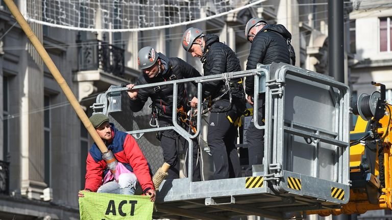 Police used a cherry picker to remove a protester locked to the top of the bamboo pyramid