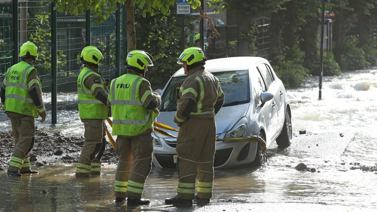 Firefighters on a flooded street in Finsbury Park, north London, after a pipe burst