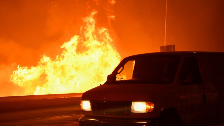 A wind-driven wildfire burns along the 210 freeway in Sylmar, California, U.S.