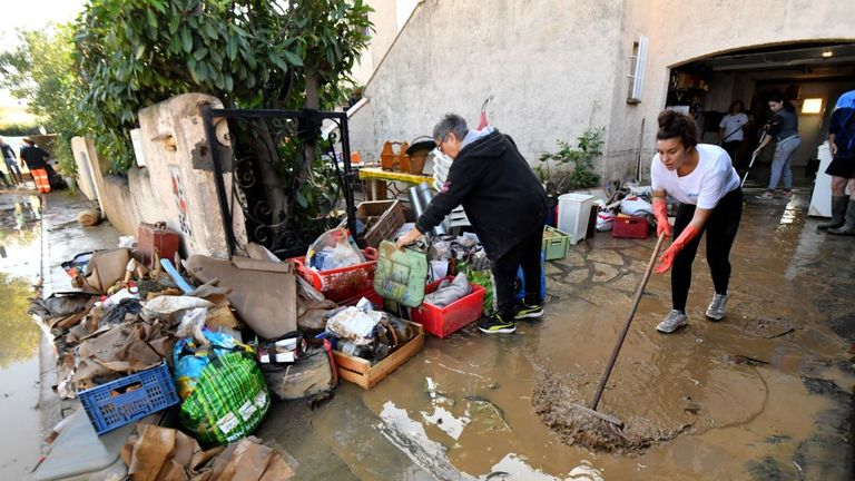 A woman in Beziers cleans her house in the aftermath of the floods