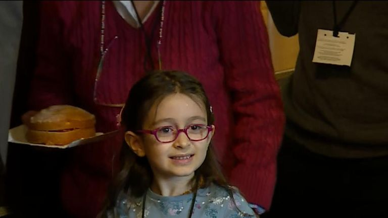 Richard Ratcliffe's daughter Gabriella arrives with a cake during a news conference in Westminster