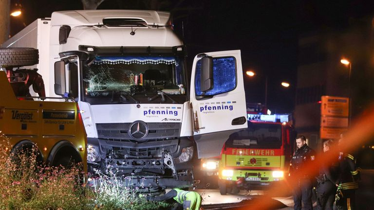 Police officers and firemen look on as a man inspects on early October 8, 2019 the truck that ploughed into several cars on late October 7 in the centre of the German city of Limburg. - The stolen truck ploughed into several cars leaving a number of people injured, police said on October 8, 2019, adding that the driver had been detained. Police said it was too soon to speculate about a motive for the incident, which began when a man seized the truck. (Photo by Yann Schreiber / AFP) (Photo by YAN