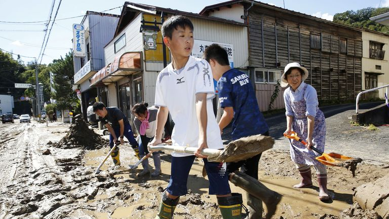 Schoolchildren and residents remove mud after flooding caused by Typhoon Hagibis in Marumori, Miyagi prefecture, Japan, October 13, 2019. Pic: Kyodo