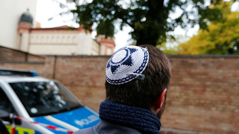 A man wearing a kippah is seen next to a police vehicle outside the synagogue in Halle