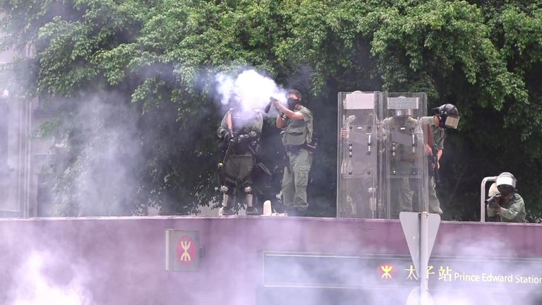 Hong Komg police officer firing taer gas.