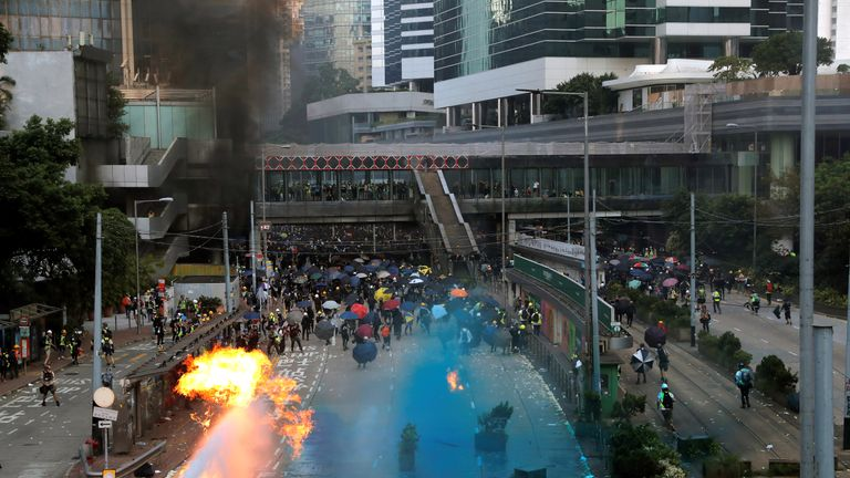 Riot police spray blue-coloured water during a protest on China's National Day in Hong Kong