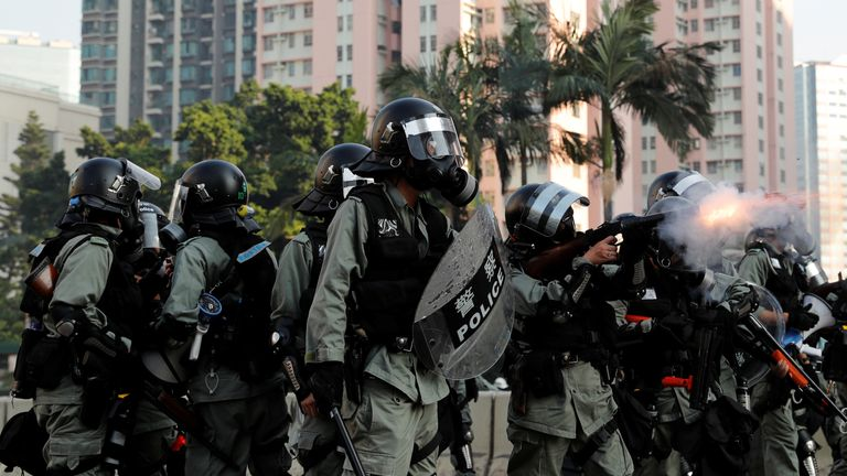 A riot police officer fires a tear gas canister