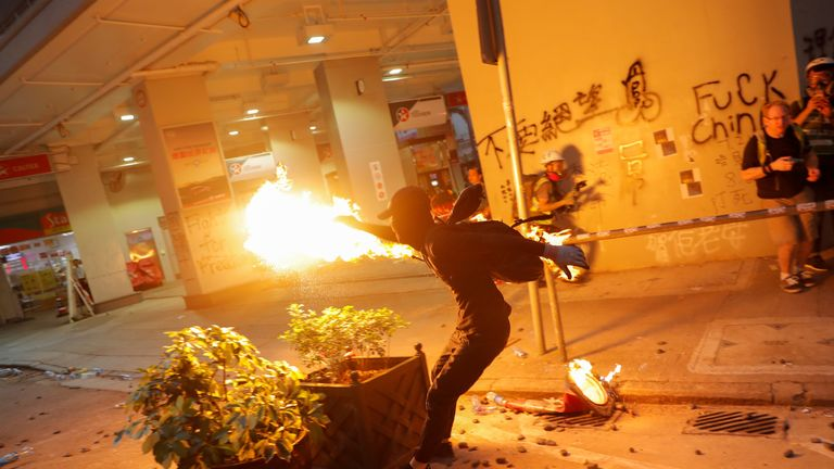 An anti-government protester throws a molotov cocktail